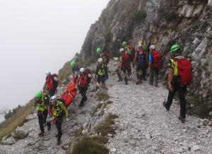 I tecnici del Soccorso Alpino riportano a valle la salma seguiti dalla comitiva di amici della persona deceduta