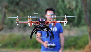 Un drone per uso civile a più eliche e sulla sfondo il pilota con il radiocomando