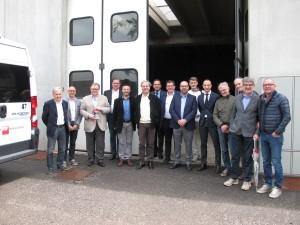 foto di gruppo tra amministratori Vicentini e Trentini davanti al deposito degli autobus di Luserna